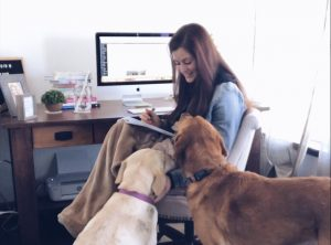woman working at her desk with dogs by her side